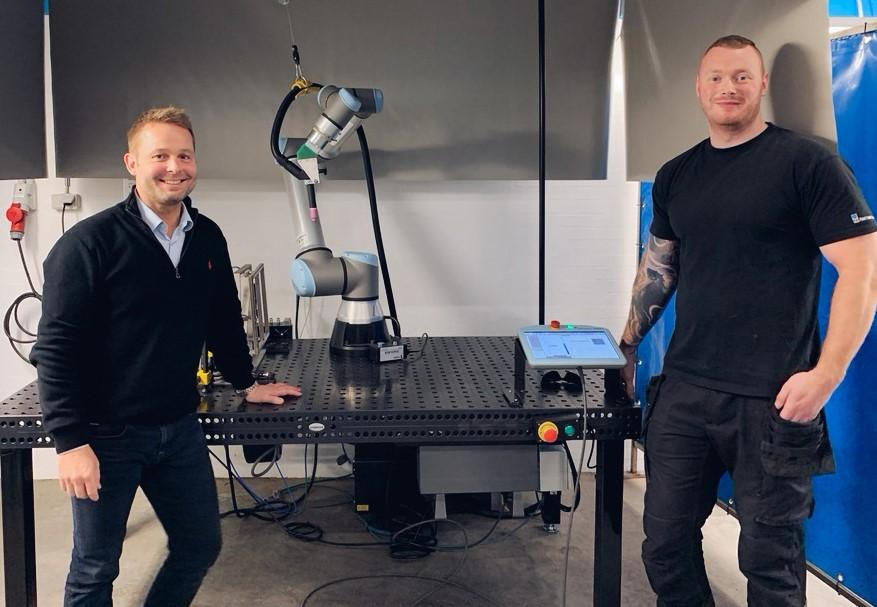 Søren og Mads fra FKI Fast Food Teknik med robotsvejser i baggrunden
